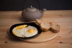Huevos revueltos con pan de centeno en una tabla de madera Tetera de cerámica japonesa en el fondo Comida de las fotos en a Imagenes de archivo