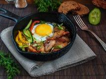 Huevos revueltos con tocino en un sartén del arrabio con el vegetab Fotografía de archivo libre de regalías
