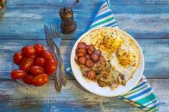 Huevos revueltos con tocino, la cebolla y la salchicha imagen de archivo