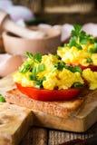Huevos revueltos en dos pedazos de tostada con la cebolla verde y el tomat Fotografía de archivo