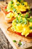 Huevos revueltos en dos pedazos de tostada con la cebolla verde y el tomat Foto de archivo