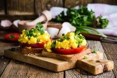 Huevos revueltos en dos pedazos de tostada con la cebolla verde y el tomat Imagen de archivo