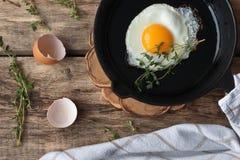 Huevos revueltos en una cacerola del hierro en la tabla rústica Imagenes de archivo
