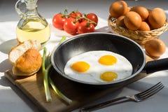 Huevos revueltos en una cacerola y los ingredientes Imagen de archivo
