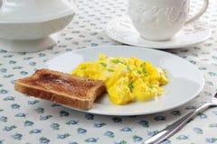 Huevos revueltos, taza de café y tostada Foto de archivo
