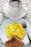 Huevos revueltos, taza de café y tostada Fotografía de archivo