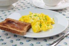 Huevos revueltos y tostada Imagenes de archivo