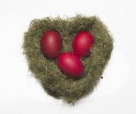 Huevos rojos en una jerarquía en un fondo blanco Imagen de archivo libre de regalías