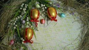 Huevos, snowdrops, hierba y tarjeta de felicitación de oro