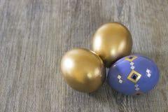 Huevos tres de Pascua decorativos en un fondo de madera gris Imagen de archivo