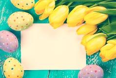 Huevos, tulipanes y tarjeta de Pascua foto de archivo