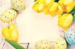 Huevos, tulipanes y tarjeta de Pascua imagen de archivo