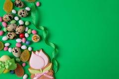 Huevos y caramelo de codornices de Pascua en lado del fondo verde con el sitio en blanco o del espacio para la copia, texto, sus  Foto de archivo