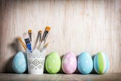 Huevos y cepillos en colores pastel de Pascua en una taza rústica imagen de archivo libre de regalías