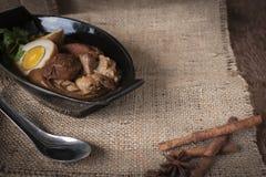 Huevos y cerdo guisado en cuenco y especias negros, lugar de acero inoxidable de la cuchara delante en del saco y fondo de madera fotografía de archivo