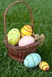 Huevos y cesta de Pascua en hierba Fotos de archivo libres de regalías