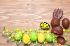 Huevos y conejito de Pascua en fondo de madera Foto de archivo