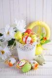 Huevos y conejo coloridos de Pascua en el fondo de madera blanco imagenes de archivo