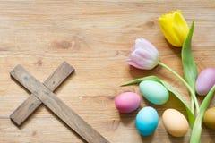 Huevos y cruz de Pascua en fondo de madera abstracto de la primavera foto de archivo
