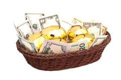 Huevos y dólares de oro en cesta Imágenes de archivo libres de regalías
