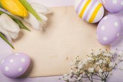 Huevos y flores coloridos de Pascua en la hoja de papel vieja Fotos de archivo libres de regalías