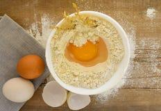 Huevos y harina en la tabla de madera fotografía de archivo