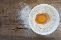 Huevos y harina en la tabla de madera imagenes de archivo