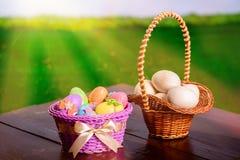 Huevos y preparaciones de Pascua para los huevos en una tabla de madera y una cesta Fotos de archivo
