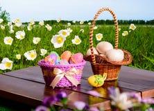 Huevos y preparaciones de Pascua para los huevos en una tabla de madera y una cesta Fotografía de archivo
