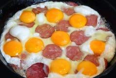 Huevos y salchicha fritos en una cacerola Imagenes de archivo