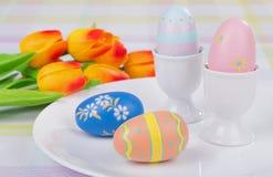 Huevos y tazas coloreados de Pascua Foto de archivo libre de regalías