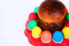 Huevos y torta coloreados de Pascua en el fondo blanco Fotos de archivo