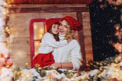 Hug each other. Happy mother and daughter in beautiful warm clothes hug each other on the porch of the house, decorated for Christmas. Seasonal winter fashion royalty free stock photos
