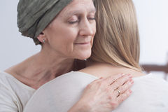 Hug full of family's love. Sick women with cancer hugging her young daughter Stock Photo