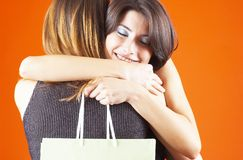 Hug For A Gift. One teenage girl hugging another, in appreciation for a gift in the bag she holds in her hand. Shot in studio with orange background