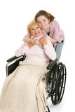 Hug For Grandmother. Senior woman in wheelchair gets hug from her teen granddaughter.  Isolated on white Stock Image