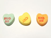 Hug me and kiss me hearts. Candy conversation hearts stock photography