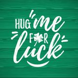 Hug Me For Luck. Handdrawn dry brush style lettering on green wooden background, 17 March St. Patrick`s Day celebration. Suitable for t-shirt, poster, etc Royalty Free Stock Photos