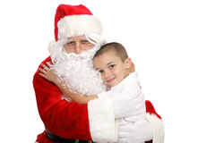 Hug For Santa. Adorable little boy giving Santa Claus a hug.  Isolated on white Royalty Free Stock Photo