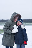 Hug in the snow. Brother and sister hug each other on a cold winters day Royalty Free Stock Image