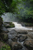 Huge active waterfall in green tropical mountain forest with peo Royalty Free Stock Photos