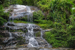 Huge active waterfall in green tropical mountain forest with peo Royalty Free Stock Images
