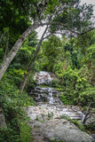 Huge active waterfall in green tropical mountain forest with peo Stock Photo