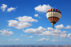Huge air balloon flying in the cloudy sky Stock Photography