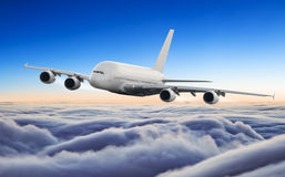 Huge airplane flying above clouds in dramatic sunset Stock Images