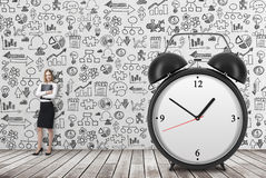 A huge alarm clock on the front view and there is a business lady with black document file. Business icons are drawn on the concre Royalty Free Stock Photos