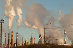 Huge amount of smoking factory. Chimneys in the sun Stock Image