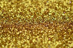 A huge amount of yellow decorative sequins. Background texture with shiny, small elements that reflect light in a random order. Gl. Itter texture Stock Photo