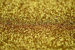 A huge amount of yellow decorative sequins. Background texture with shiny, small elements that reflect light in a random order. Gl. Itter texture Stock Photos