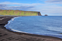 Huge arched beach with black sand. On the horizon are visible rocks in the sea. Cape Dirholaey in southern Iceland stock images